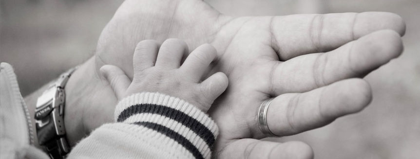 A baby's hand rests in a masculine older hand.