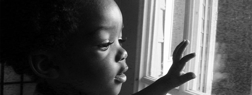 A baby stares outside of a sunlit window
