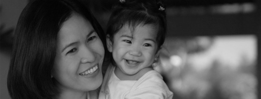 A woman of Asian descent holds her daughter in her arms, both smiling.